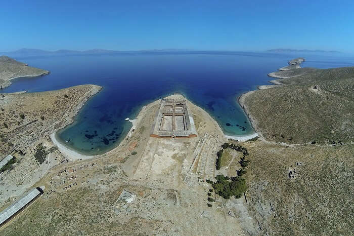 An aerial shot of the island of Gyaros in Greece along with the azure waters surrounding it