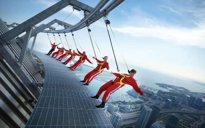People wearing red clothes hanging from Macau Tower