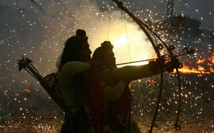 Actors dressed as lord rama taking aim at an effigy during dussehra celebrations