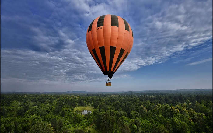 A hot air balloon in the sky above green forest