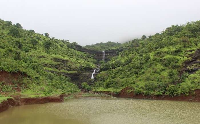 A waterfall amid green valleys
