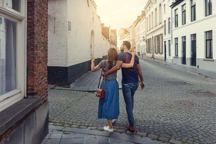 a couple walking through the streets of Belgium on their honeymoon