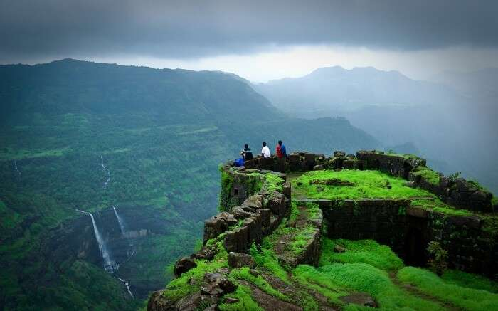 Three men standing at the edge of a fort in mountains