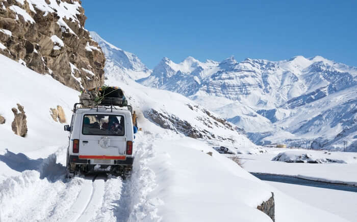 A jeep moving on a road covered in snow in Spiti during winter