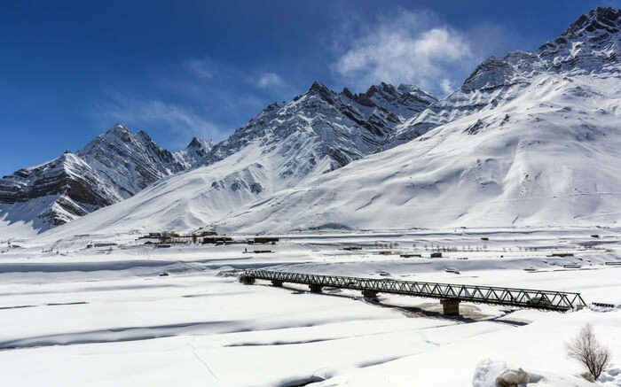 A bridge in Spiti valley overlooked by snow covered mountains