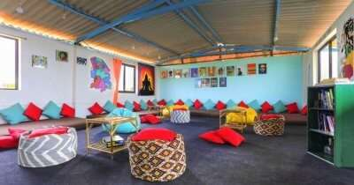 a sitting room of a hotel with colorful pillows