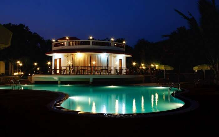 A well lit Golden Toff Resort with a glittering swimming pool at night