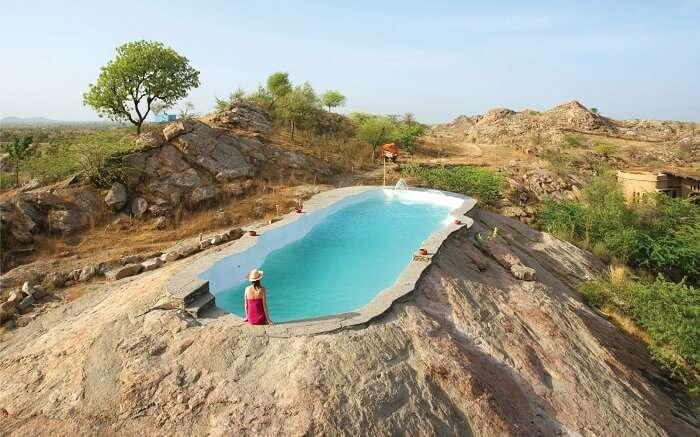 A woman sitting beside the rock-cut pool of Lakshman Resort
