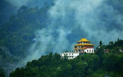 View of a monastery in Sikkim surrounded by lush greenery and fog