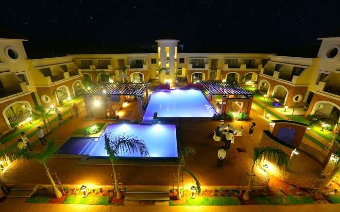 Two outdoor pools and a well lit lawn of a hotel