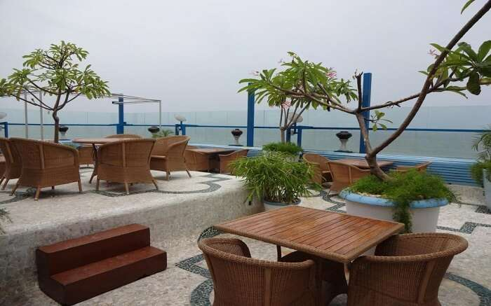 Wooden tables and chairs on a terrace overlooking the ocean