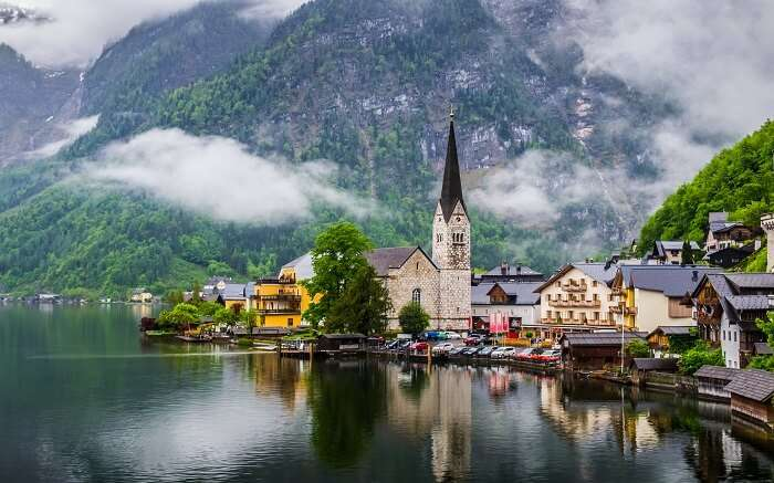 an incredibly gorgeous view of churches and homes by a lake