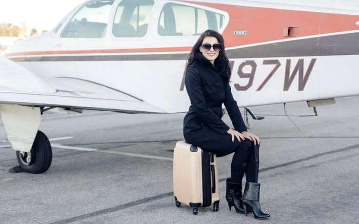 Jill Paider posing for a photograph on her suitcase