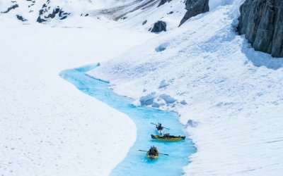 Travelers kayaking in a lake in glacier in Canada