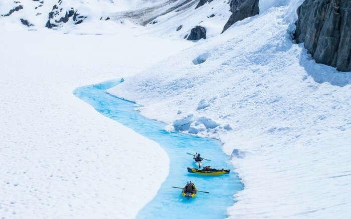 Travelers kayaking in a lake in glacier in Canada