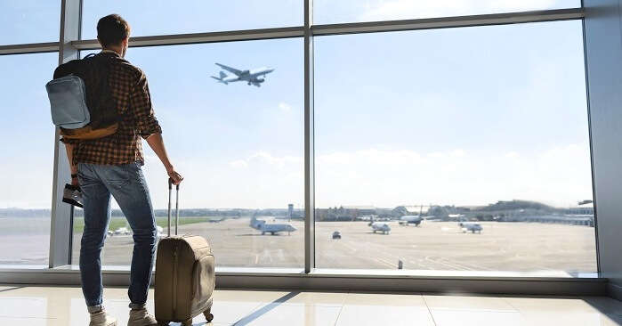 man waiting for flight at airport