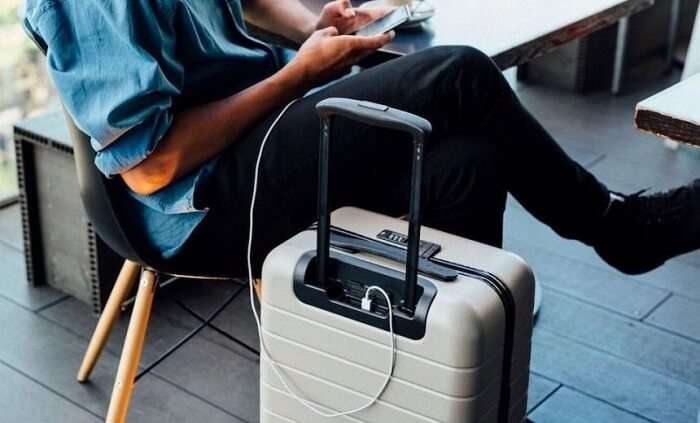traveler charging phone from smart luggage