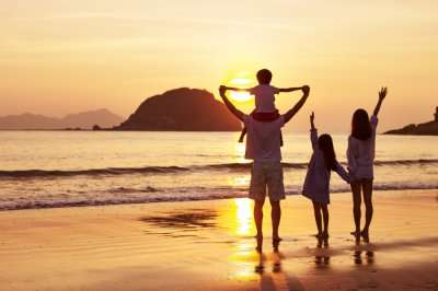 a family standing on a beach during sunset in hong kong