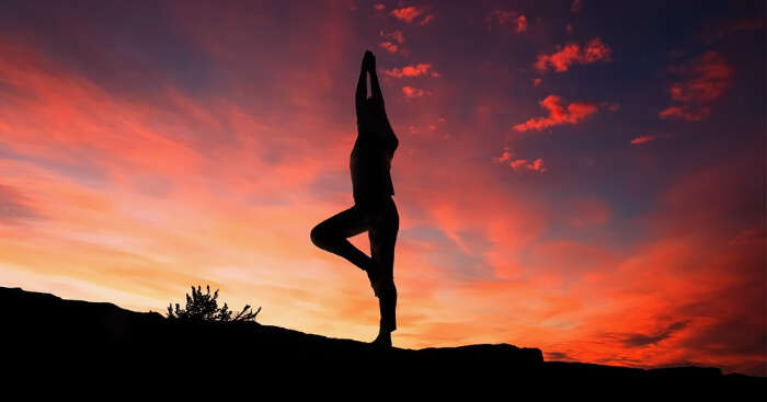 somebody doing yoga during twilight