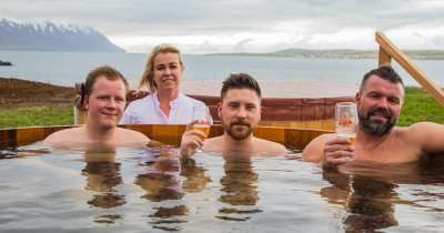 people in a wooden tub filled with beer