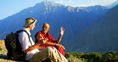 a monk sitting with a tourist
