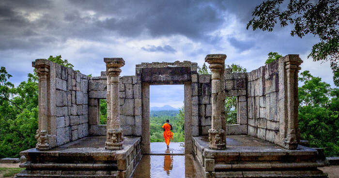 a monk standing at a ruined structure