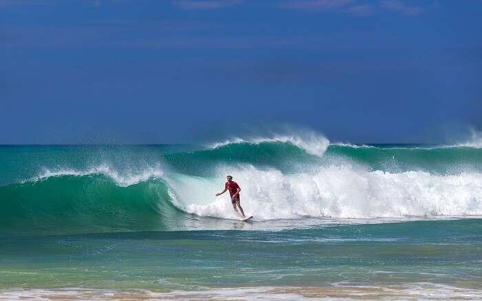 a man surfing on high tides