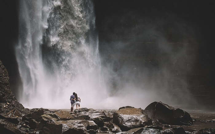 a couple standing below a waterfall