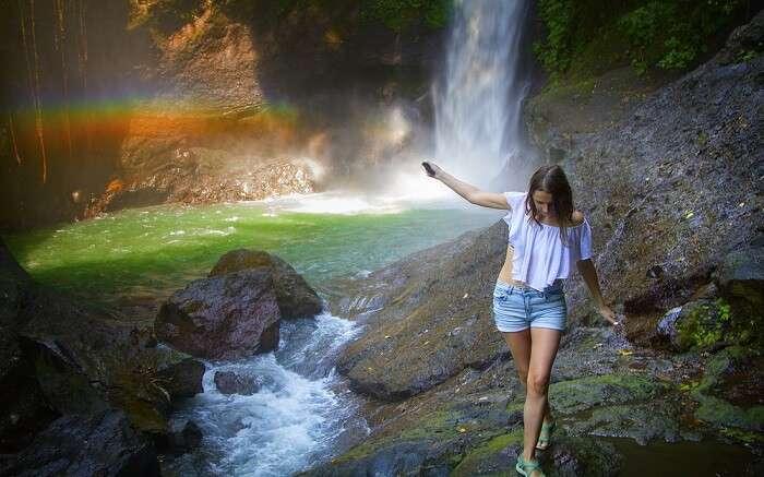 a women walking along a rainbow waterfall