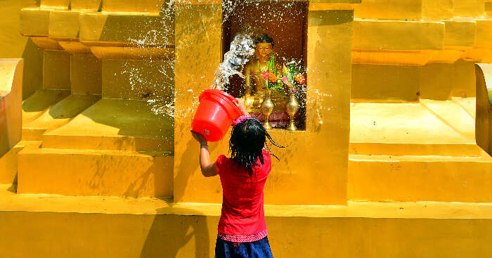 A girl washing the Buddha idol in Namphake Village in Dibrugarh, Assam