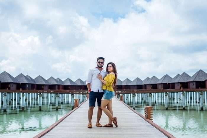 couple posing in front of villas in maldives