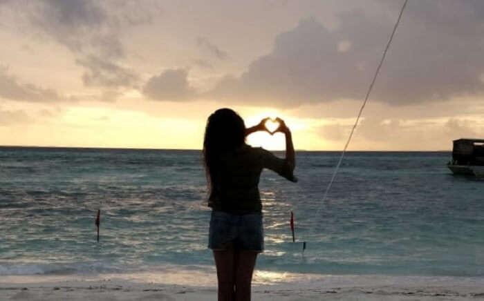 girl making heart on the beach