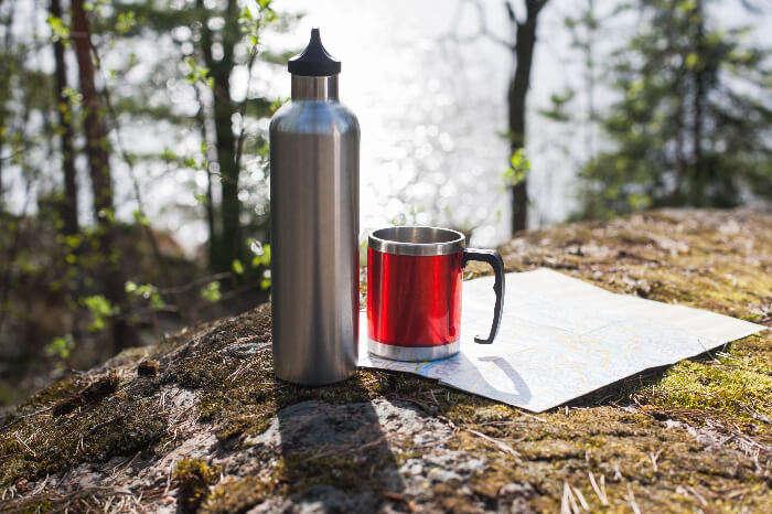 Thermal Bottle and mug kept on a hill side