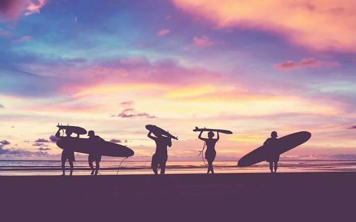 people carrying surfing boards at El Porto Beach