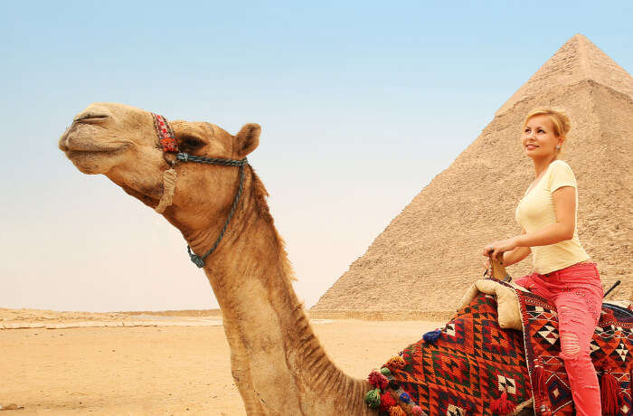 A woman on a camel near a pyramid inn Egypt