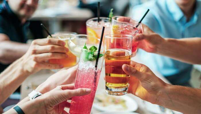 people clinking their glasses with cocktail and mocktail