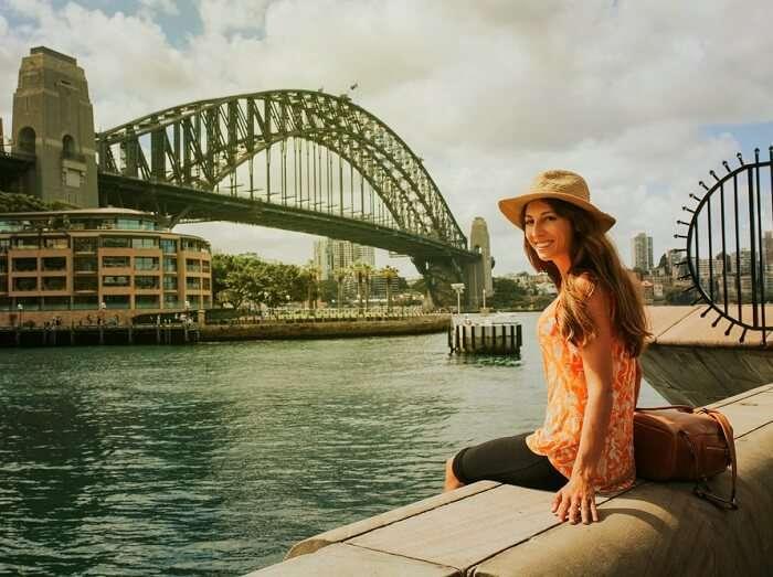 Girl sitting in front of harbour bridge