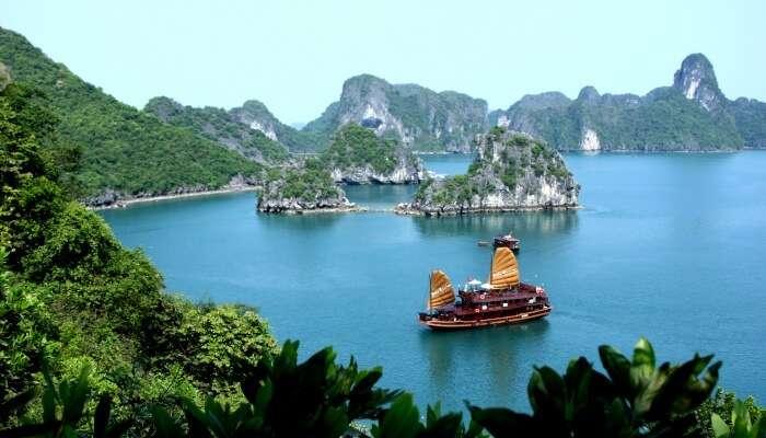 cruise ship moving around cliffs
