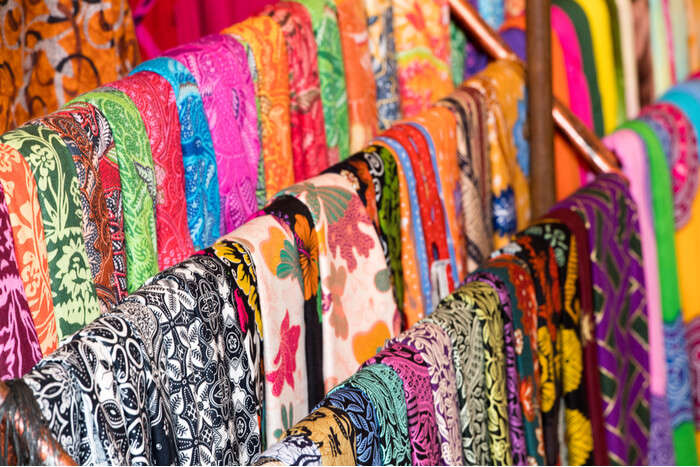 stoles hanging in a market in bali