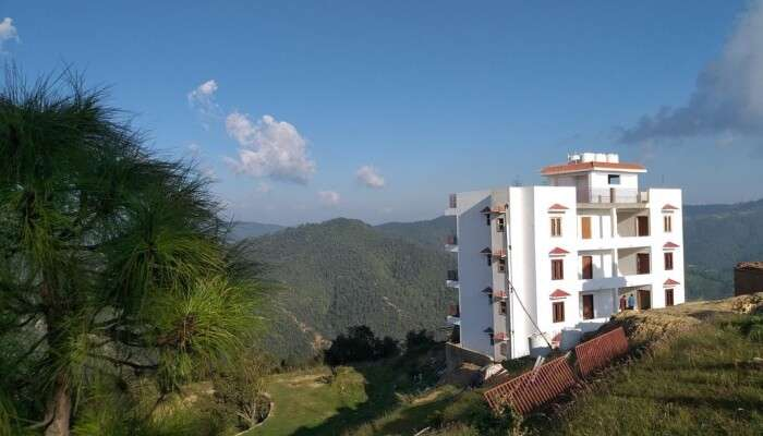 white building amidst green mountains