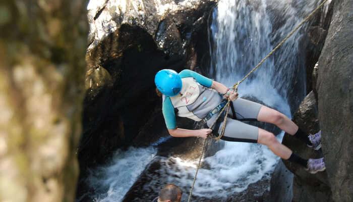 A girl enjoying waterfall rappelling