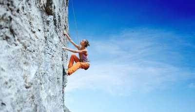 A woman enjoys rock climbing adventure